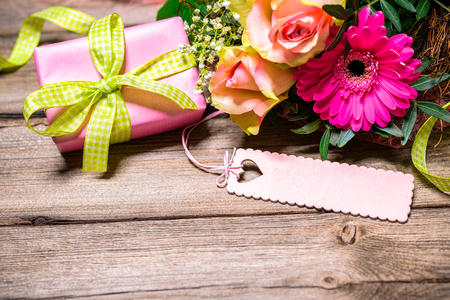 Background with bouquet of flowers, gift box and an empty tag on wooden board