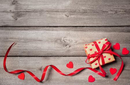 Valentinstag Vintage Hintergrund mit Herzen und ein Geschenk-Box auf einem Holzbrett