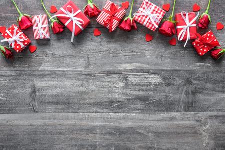 Fondo del día de San Valentín de la vendimia con las rosas y cajas de regalo en la tabla de madera