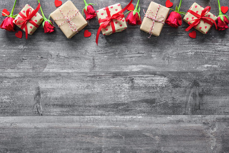 flower boxes: Valentines day vintage background with red roses and gift boxes on wooden board Stock Photo