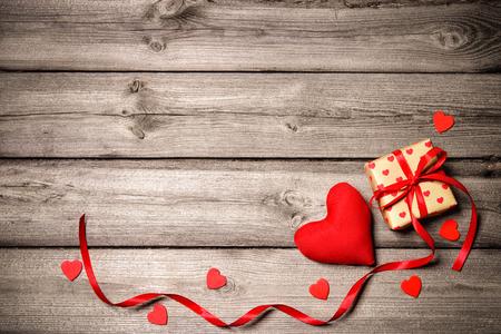 De uitstekende achtergrond van de valentijnskaartendag met harten en een giftdoos op houten raad