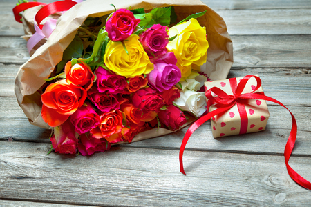 anniversary flower: Background with bouquet of roses and gift box on wooden board Stock Photo
