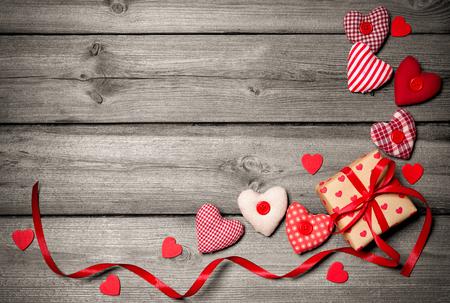 dia: fondo de la vendimia de San Valentín con corazones y una caja de regalo sobre tabla de madera