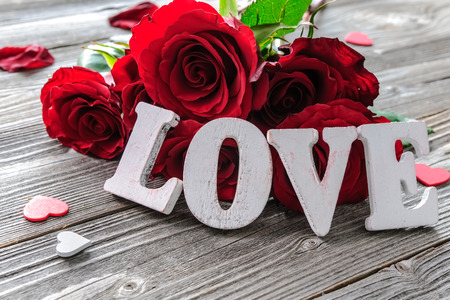 Red roses flowers and word love on wooden background Stockfoto