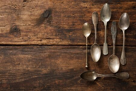 rustic kitchen: Vintage metal spoons on wooden table