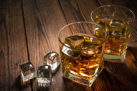 table glass: Glasses of whiskey with ice on wooden table