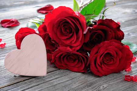 mazzo di fiori: Rose rosse e cuore su sfondo di legno. San Valentino sfondo Archivio Fotografico