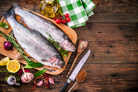 seasoning: Fresh trout with spices and seasoning on cutting board Stock Photo