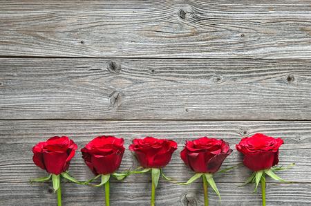 Rosas rojas en la tabla de madera, día de San Valentín Foto de archivo - 50773459