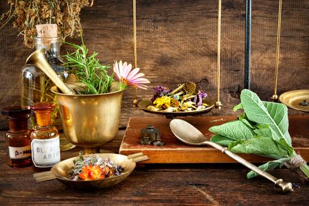 Oude natuurlijke geneeskunde, kruiden, flesjes en schaal op houten achtergrond Stockfoto