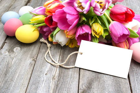 green flowers: Easter eggs and tulips with a tag on wooden background