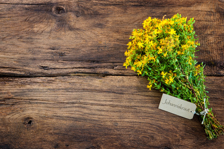 wild herbs: Hypericum perforatum or St johns wort with a tag on wooden background Stock Photo