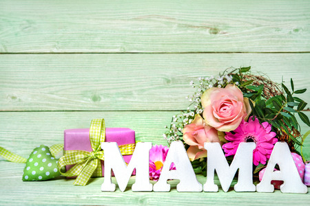 mother: Bunch of roses with a gift box and word Mama on wooden background