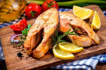 circuito integrado: Grilled salmon steaks with vegetables on cutting board