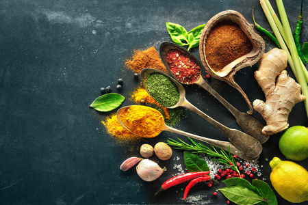 food additives: Various herbs and spices on black stone plate Stock Photo