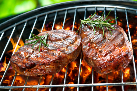 meat on grill: Grilled beef steaks over the coals on a barbecue Stock Photo