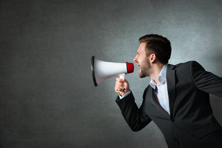 communicating: Young handsome shouting man using megaphone over grey background Stock Photo