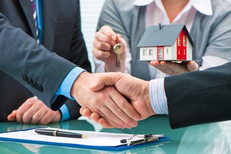 Agente immobiliare agitando le mani con il cliente dopo la firma del contratto Archivio Fotografico