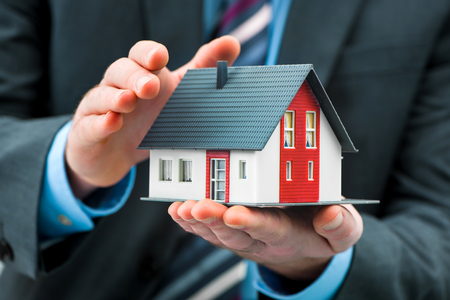 Realtor: Hands presenting a small model of a house Stock Photo