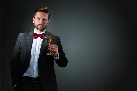 Proost-De jonge man met een groot cocktailglas op donkere grijze achtergrond Stockfoto
