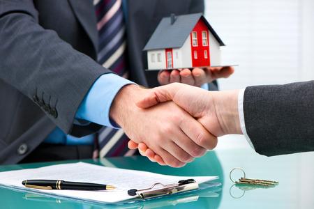 apreton de mano: Agente de raíces, agitando las manos con el cliente después de la firma del contrato Foto de archivo