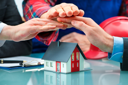 household insurance: Hands as a protecting roof over a little house