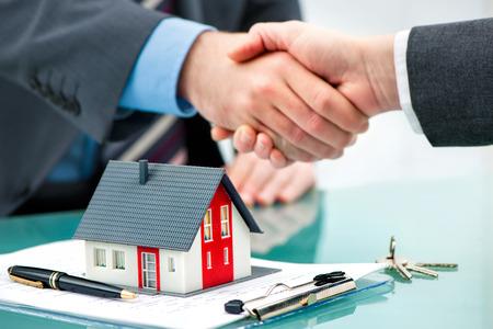 negociacion: Agente de ra�ces, agitando las manos con el cliente despu�s de la firma del contrato Foto de archivo
