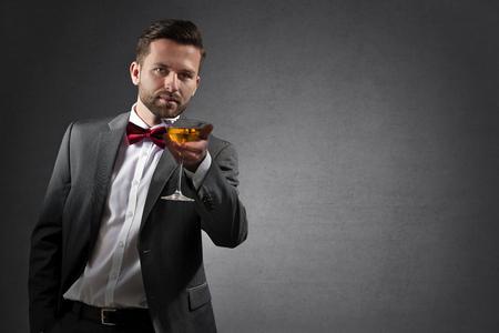 Vive-jeune homme tenant un verre à cocktail de haut sur fond gris foncé