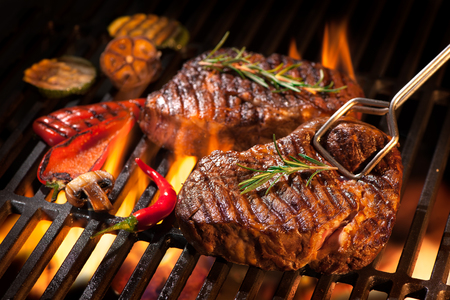 flames: Beef steaks on the grill with flames
