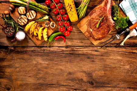 barbecuing: Beef steak with grilled vegetables and seasoning on wood Stock Photo