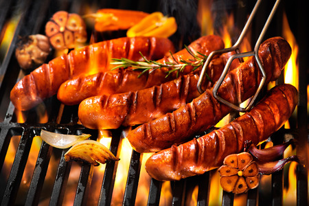 Grilled sausage on the flaming grill
