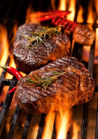 Rindersteaks auf dem Grill mit Flammen Standard-Bild