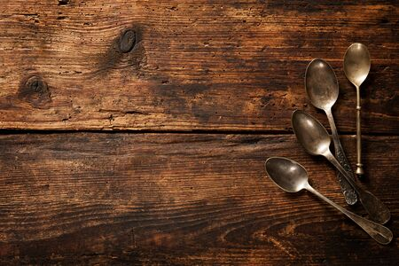 stainless steel background: Vintage metal spoons on wooden table