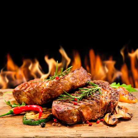 blazing: Delicious beef steakes on wood Stock Photo