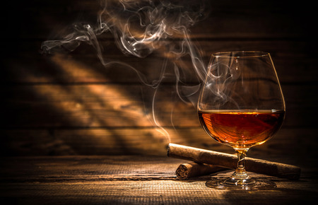 Glass of whiskey with smoking cigar and ice cubes on wooden table