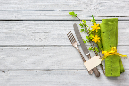 Spring table place setting with daffodils. Holidays background