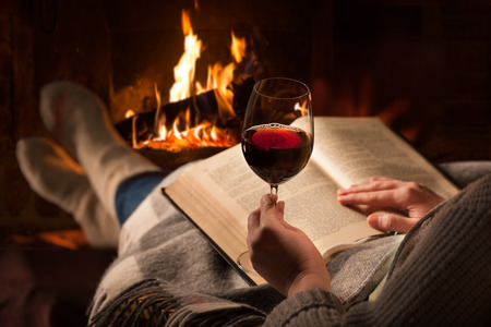 home keeping: Woman resting with glass of red wine and book near fireplace
