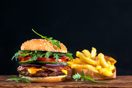 Delicious hamburger with french fries on wooden table Reklamní fotografie - 54094141