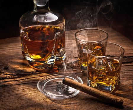 glass background: Glasses of whiskey with smoking cigar on wooden table Stock Photo