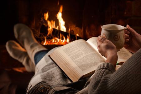 Mujer que se reclina con la taza de bebida caliente y el libro cerca de la chimenea Foto de archivo - 54094138
