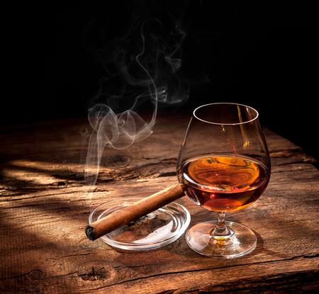 나무 테이블에 시가 흡연과 얼음 조각으로 위스키의 유리
