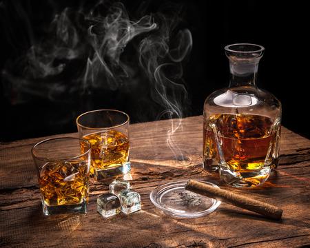Glazen whisky met roken sigaar en ijsblokjes op houten tafel Stockfoto