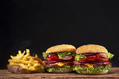 おいしいハンバーガーと木製のテーブルのフライド ポテト 写真素材