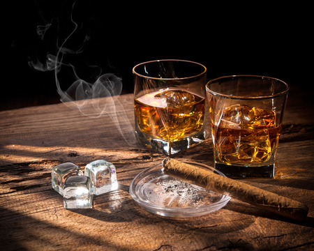 Glasses of whiskey with smoking cigar and ice cubes on wooden table Reklamní fotografie - 54094153
