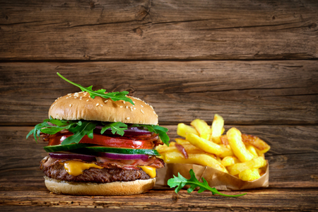 Delicious hamburger with french fries on wooden table Фото со стока