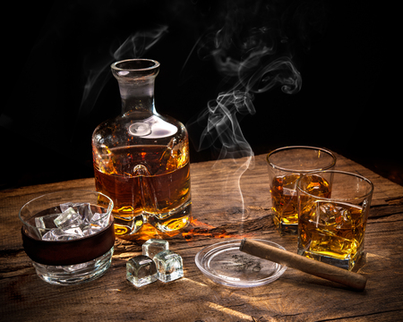 Glasses of whiskey with smoking cigar and ice cubes on wooden table