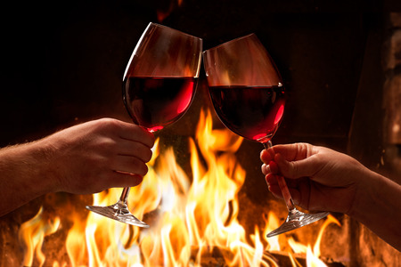 Hands toasting wine glasses in front of lit fireplace 스톡 콘텐츠