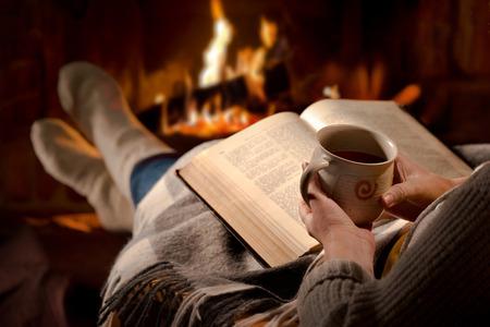 Frau ruht mit Tasse heißes Getränk und Buch in der Nähe Kamin