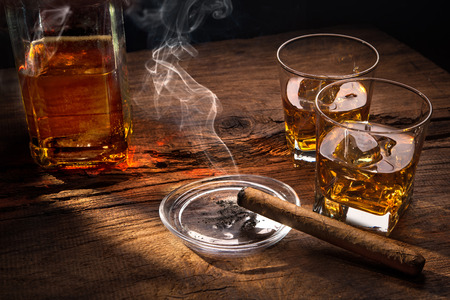 Glasses of whiskey with smoking cigar on wooden table Foto de archivo