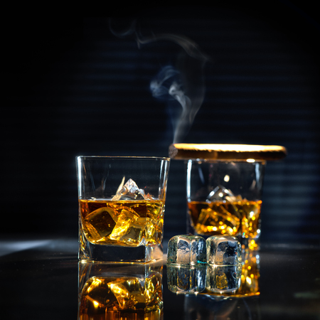 glass table: Glasses of whiskey with smoking cigar and ice cubes on dark background